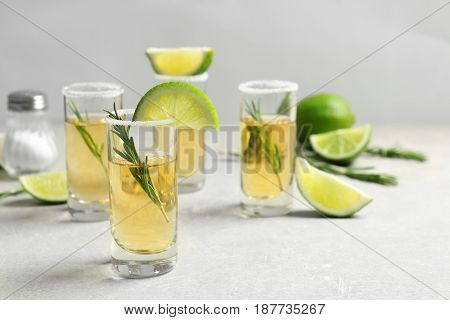 Golden tequila shots with juicy lime slices, rosemary and salt on light background