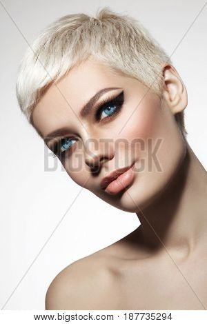 Beautiful blonde woman with short hair cut and stylish winged eye make-up, copy space