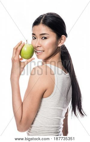 Happy Asian young woman looking at camera while holding a green apple against white background