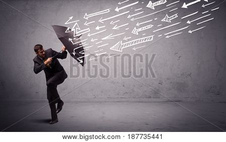 Business man standing with umbrella and drawn arrows hitting him on grungy background