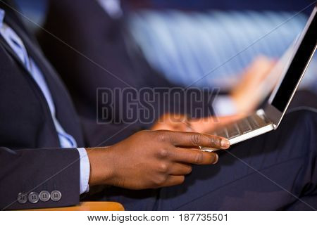 Mid section of male business executive using laptop at conference center