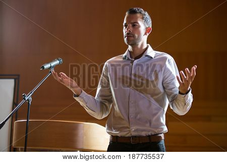 Business executive gesturing while giving a speech at conference center