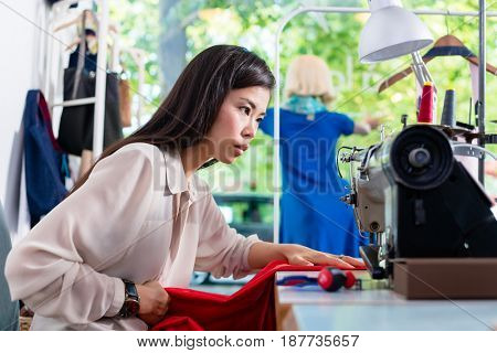 Asian tailor woman sewing dress with machine in her workshop