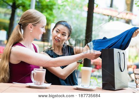 Pretty Asian woman showing a friend her purchase of a blue garment as they sit at a restaurant table enjoying refreshments