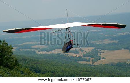 Hang Glider Soaring Over Mountainside