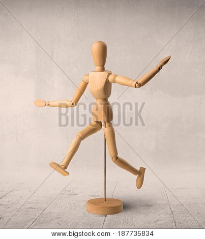Wooden mannequin posed in front of a greyish background