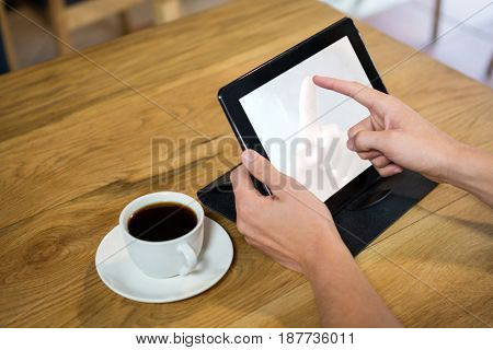Close-up of young man using digital tablet with blank screen in coffee shop