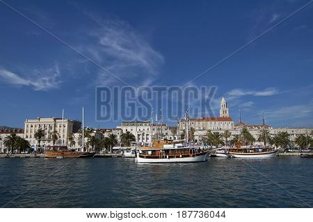 Split view on south part of old town behind sea and boats are Diocletian's palace and St Domnius cathedral