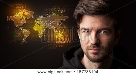 Portrait of a young businessman with a world map and numbers next to him on a dark background