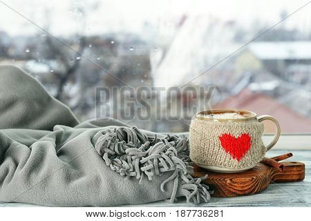 Cup of hot tasty coffee with warm plaid and wooden board on windowsill