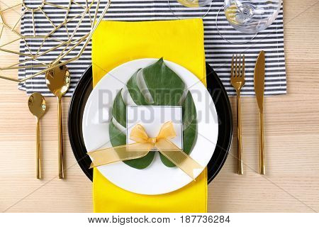 Table setting with yellow color napkin and floral decor on wooden surface