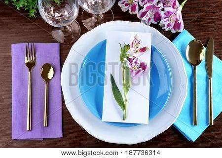 Beautiful festive table setting with floral decor on wooden surface