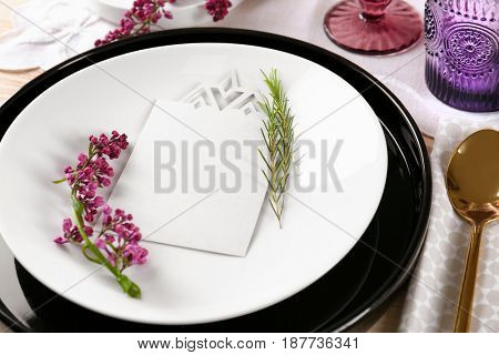 Table setting with cream color napkin, blank card and lilac floral decor on wooden surface