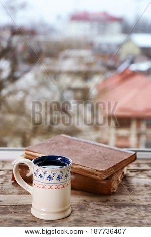 Patterned ceramic cup of hot tasty drink and old books on wooden windowsill