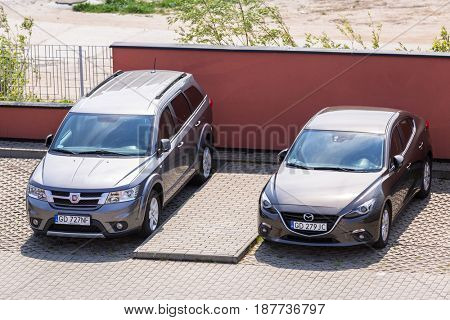 POLAND - MAY 21, 2017:  Fiat Freemont and Mazda 3 at the parking side in Poland. Fiat Freemont is an european version of Dodge Jurney manufactured sience 2011.
