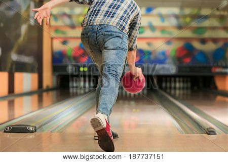 Young man throwing ball in bowling club