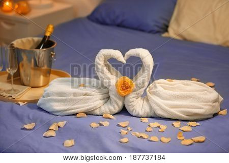 Composition with swans made of towels and rose petals on bed in hotel room. Honeymoon concept