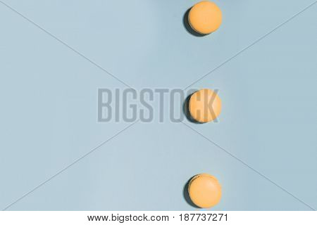 Picture of three sweet yellow macaroons on blue table background.