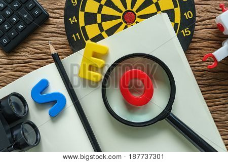 SEO optimization concept with pencil dartboard robot calculator and binoculars on paper note.