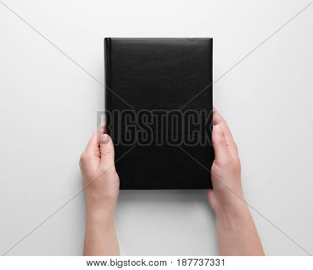 Female hands holding closed book with black blank cover on white background