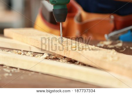 Carpenter drilling wooden board in workshop, closeup