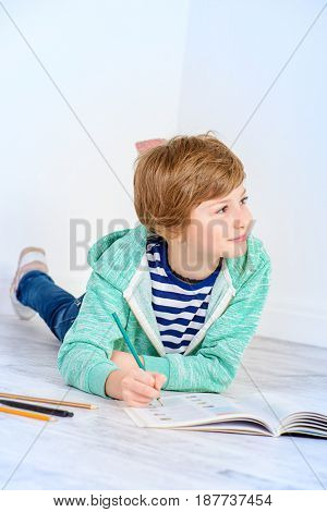 Cute nine-year girl diligently doing her homework. Educational concept.
