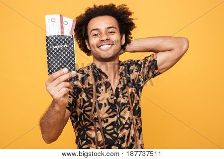 Image of young smiling man standing isolated over yellow background. Looking at camera holding passport.