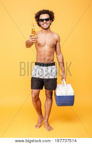 Picture of cheerful young african man dressed in shorts standing isolated over yellow background. Looking at camera holding beer.