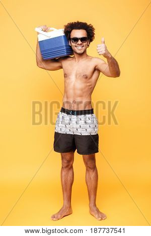 Full length portrait of a positive young african guy in sunglasses holding icebox and showing thumbs up gesture over yellow background