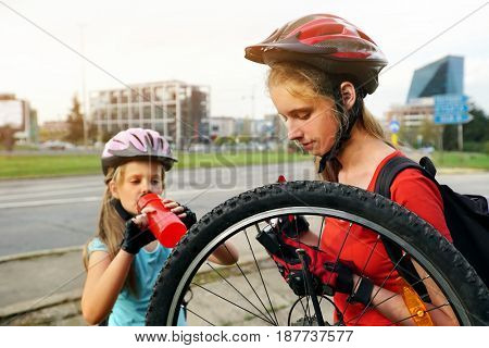 Bicycle tire pumping by child bicyclist . Kid wearing bicycle helmet with hand pump for bicycle. Girl drink bottle water. There are road and traffic sign at background. Small rest in journey