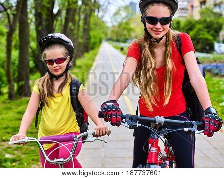 Bicycle path with children. Girls wearing bicycle helmet with rucksack ciclyng ride. Kids or mother with daughter are on yellow bike lane. Alternative to urban transport. Flowerbed with flowers in