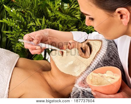 Collagen face mask. Facial skin treatment. Face of woman of elderly woman 50-60 years old receiving cosmetic procedure in beauty salon close up number one isolated. Fern in the background.