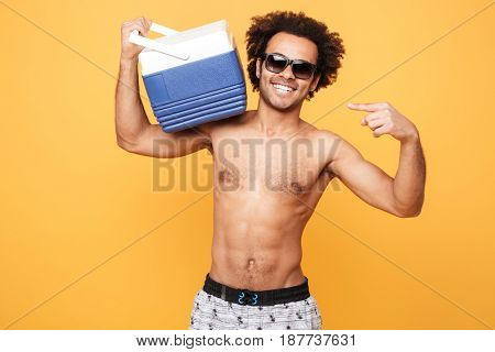 Portrait of a young afro american man in summer shorts holding and pointing at icebox over yellow background