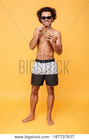 Picture of handsome young african man dressed in shorts standing isolated over yellow background. Looking at camera drinking cocktail.