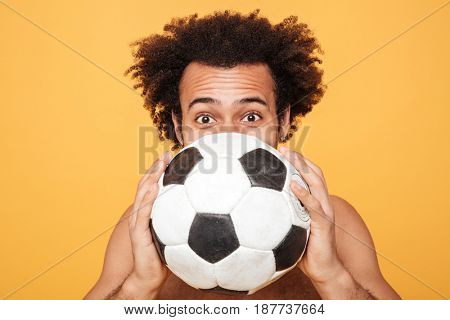 Close up portrait of a young african man hiding face behind a foot ball over yellow background