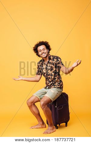 Full length portrait of a happy young afro american man in summer clothes sitting on a suitcase with hands outstretched isolated over yellow background