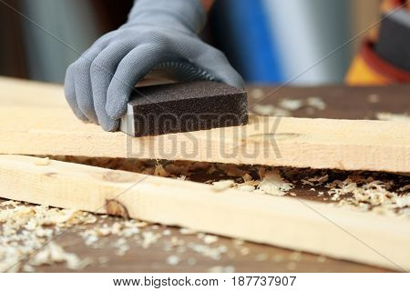 Hand of carpenter machining wooden board with abrasive stone, closeup