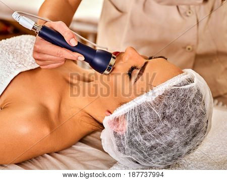 Ultrasonic facial treatment on ultrasound face machine. Woman has electric lift massage spa salon. Stimulation muscles on equipment microcurrent therapy . Modern technologies and methods rejuvenation. poster
