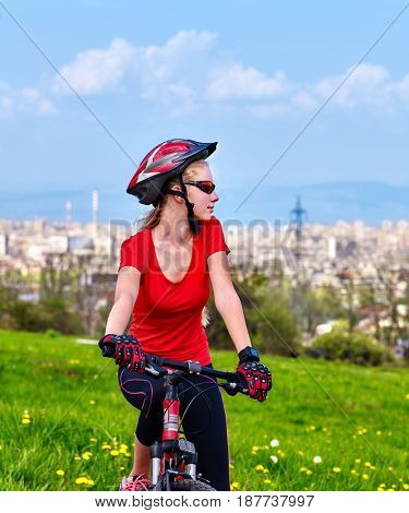 Escape urban . Bicycle girl has rest from city bustle. Woman wearing sport helmet rides returns into urbanization . Factory pipes in background.