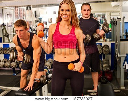 Woman holding dumbbell workout at gym. Cropped shot of of middle section of bare belly. Friends men on background. Body that you want concept. Girl decided to start playing sports.
