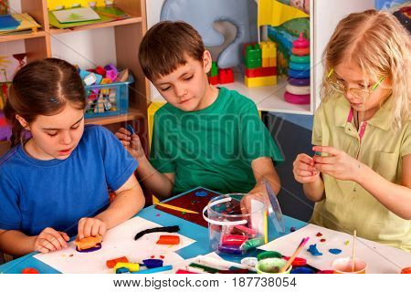 Plasticine modeling clay in children class. Teacher teaches kids together play dough and mold from plasticine in kindergarten or preschool. Group of four people. Collective creativity.