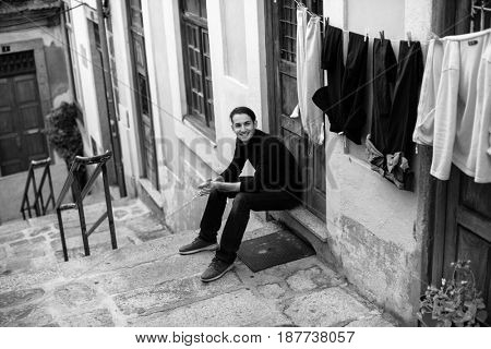 Young fashionable guy on the streets of a European town, sitting on the porch of the house. Black-and-white photo.