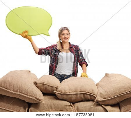Female farmer with a speech bubble behind a pile of burlap sacks isolated on white background