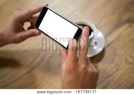 Close-up of man hands photographing coffee through smartphone in cafe