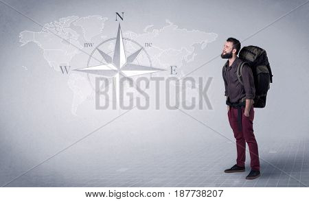 Handsome young man standing with a backpack on his back and a compass and a world map in the background
