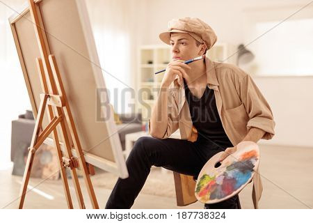 Pensive teenage painter looking at a canvas in an art studio