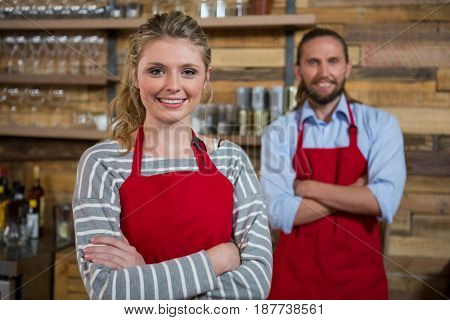 Portrait of smiling female barista with male coworker in coffee shop