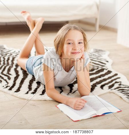 Child reading book at home. Girl lying and read indoors