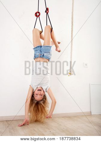 Girl on the wall bars. Child at wall bars do sport exercises