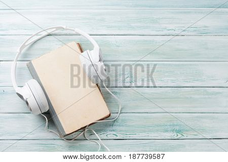 Audio book concept. Headphones and old book over wooden table. Top view with space for your text